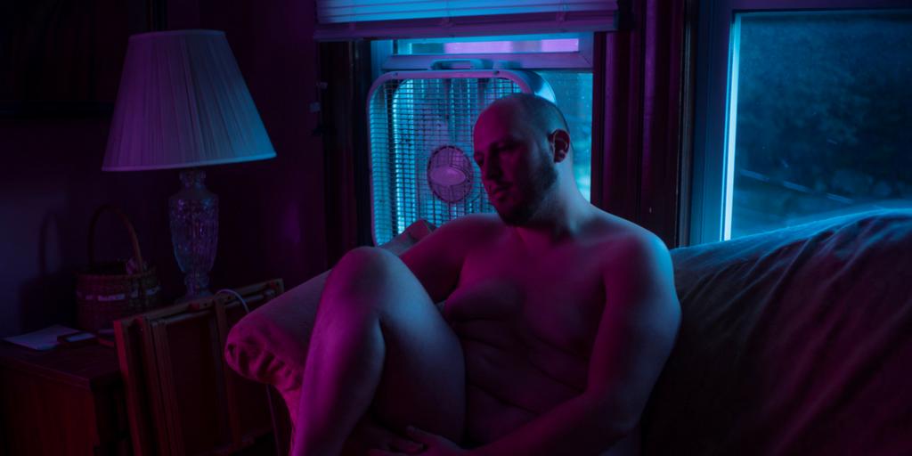 instgrmer body positive siedzący nago na kanapie w swoim salonie