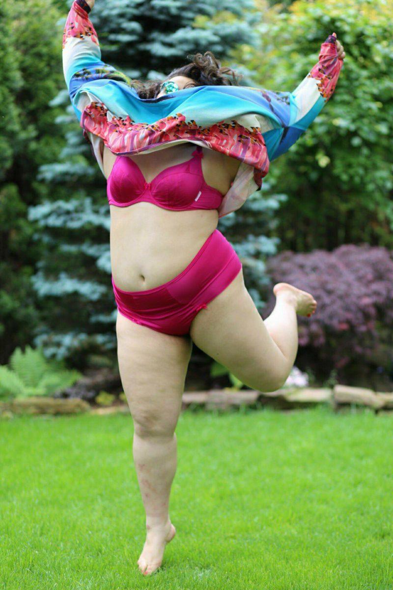 Galanta Lala wyskakuje w powietrze. Grube ciało ma ubrane w różową bielinę, wokół głowy ma bluzę w locie, która zasłania jej twarz