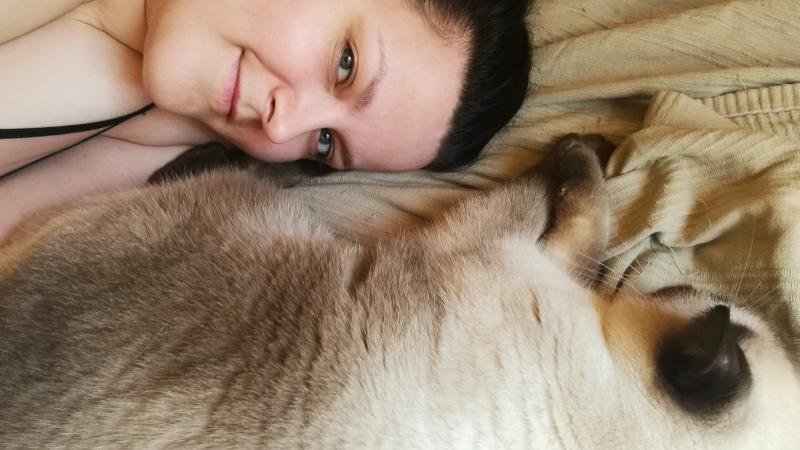Galanta Lala leży na łożku ze swoim wielkim białym kotem o ciemnej twarzy
