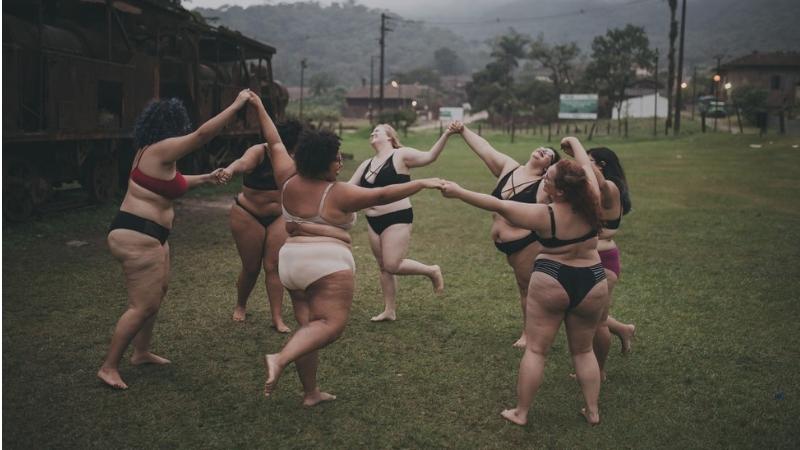 grupa grubych kobiet tańczy w samej bieliźnie, trzymając się za ręce