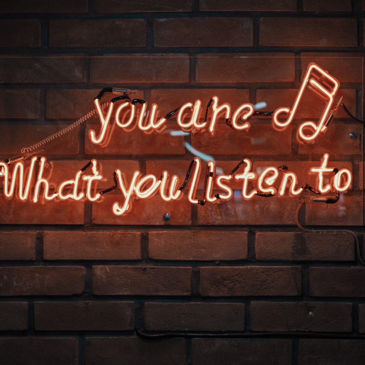 "ceglana ściana, a na niej neon z napisem ""you are what you listen to"""